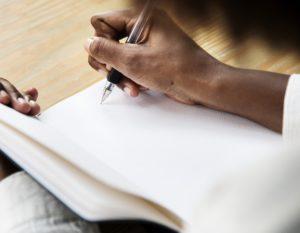 Hand som skriver i skrivbok