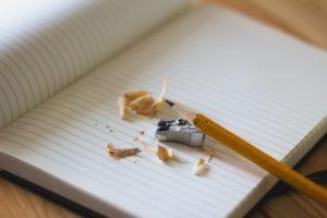 Skrivblock med blyerstpenna och pennvässare.