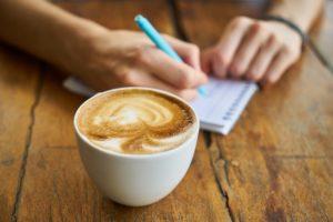 Kaffekopp på ett bord och en hand som antecknar i ett block.